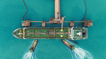Tug boats drag Oil ship tanker park to port for transfer crude oil to oil refinery.