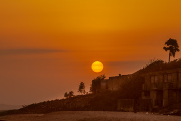 Photo sur Plexiglas Marron Bright orange sun setting over the beach of Cape Coast, Ghana