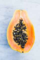 Papaya fruit half with seeds on white marble table.
