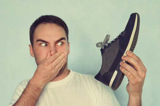 A man pinches his nostrils closed over the odor given off from the athletic shoe he is holding