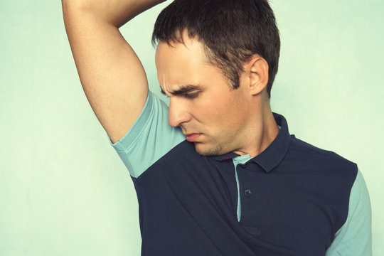 Closeup portrait of young man, smelling, sniffing his armpit, something stinks, very bad, foul odor situation, on blue wall background. Negative emotion, facial expression, feeling.