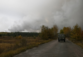 An Emergency Service vehicle drives along a road in the settlement of Druzhba, as smoke rises after a fire and explosions hit the Ukrainian defence ministry ammunition depot in the eastern Chernihiv region