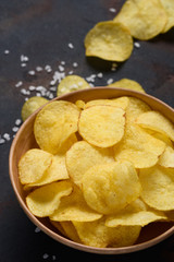 Crispy potato chips with salt in bowl