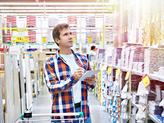 Man chooses wall tiles for bathroom in supermarket building materials