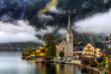 Fantastic Foggy Sunrise in the Mountains Lake. Classic postcard view of famous Hallstatt lakeside town in the Alps a beautiful Warm sunny morning with fog and clouds in autumn, Salzkammergut, Austria.