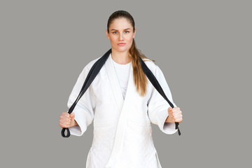 Confident attractive athletic woman in white kimono standing and wraps black belt around the neck, looking at camera. Japanese karate and sports concept. Indoor, studio shot, isolated, grey background