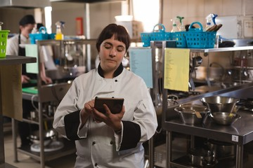 Female chef using digital tablet in kitchen