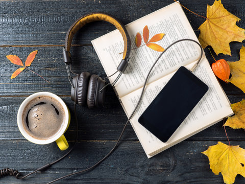 Autumn leaves, coffee, telephone with headphones and audio book concept, modern electronic library