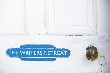 Writers retreat door sign at entrance to quiet room on white weather oak door distressed paint