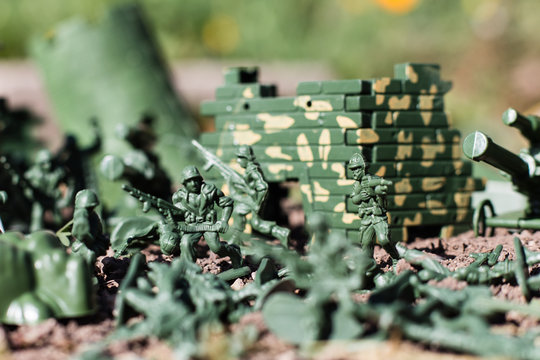 plastic toys. figures of small green armed soldiers fighting each other.