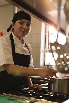 Female chef tasting food in kitchen