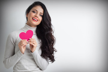 Woman holding pink paper heart