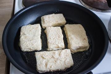 Frying coated cheese Eidam in breadcrumbs