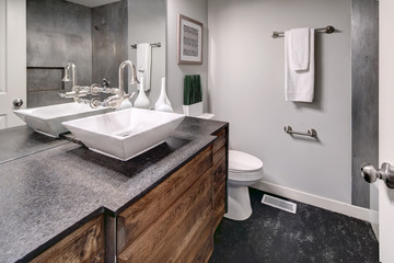 Luxurious bath with grey vanity cabinet.