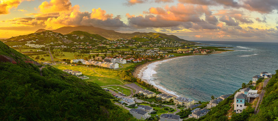 Panorama of Saint Kitts and its capital Basseterre during sunset, beautiful green mountains and a beach in paradise caribbean island with amazing green and orange colors. Saint kitts and nevis