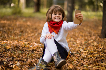 Portrait of funny little girl grimacing while taking selfie over autumn background