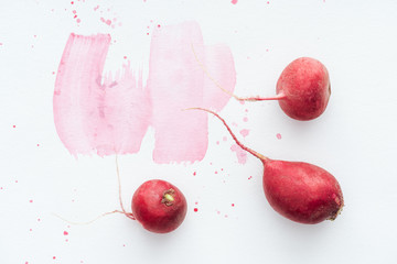 top view of ripe radishes on white surface with pink watercolor strokes