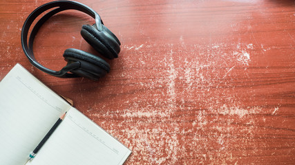 Wall Mural - headphones and earphone with notebook on wood table