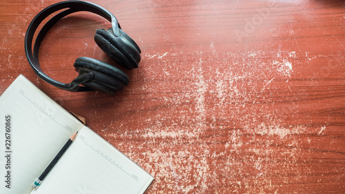 Wall mural headphones and earphone with notebook on wood table