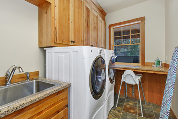 Laundry room interior with sink and wooden cabintes