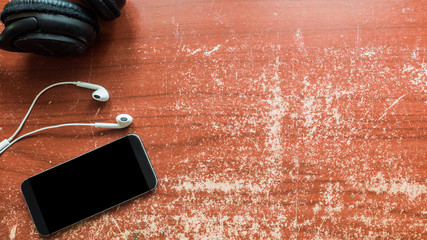 Wall Mural - smartphone and earphone on wood table