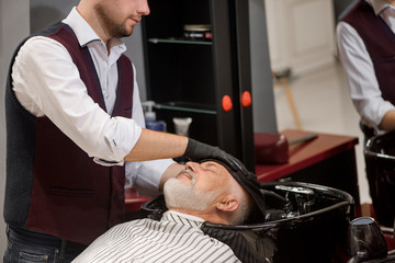 Hairstylist wiping head of client with towel in wash basin.