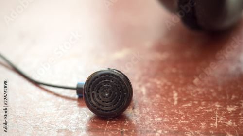 Wall mural black earphone white on wood table close up