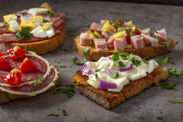 Set of open sandwiches with boiled eggs, cucumbers, salami, cheese and smoked meat