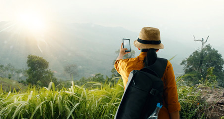 Backpacker using smartphone taking a photo of  beautiful landscape on mountain peak while exploring, trekking in tropical rain forest of Asia