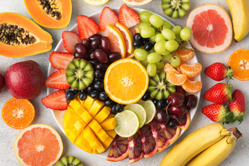 Wall Mural - Raw fruits berries platter, mango, oranges, kiwi strawberries, blueberries grapefruit grapes, bananas apples on the white plate, on the off white table, top view, selective focus