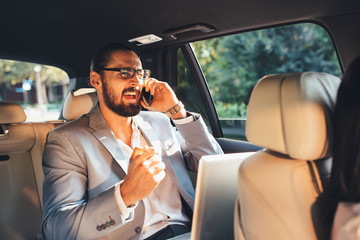 Businessman talking on the phone in a taxi