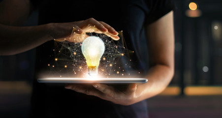 Abstract business. Human hands holding light bulb glowing on tablet and network connection communication on virtual interface, Innovation and technology concept.