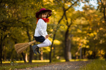 Funny little girl flies on broom in autumn park