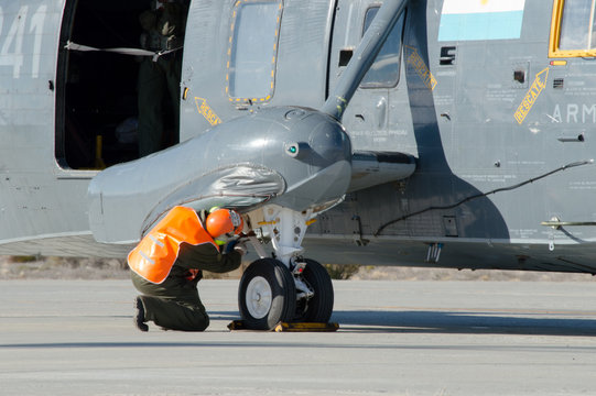 Unidentifiable mechanic, ground check, inspection of a military sea king helicopter principal landing gear