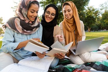 Women students using laptop computer and holding books in park.