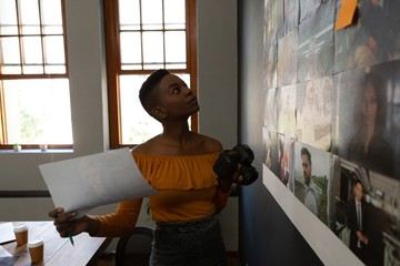 Female executive looking at photos in wall