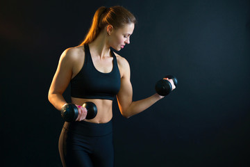 beautiful young girl goes in for sports with dumbbells on a black background