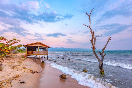 Burundi Bujumbura lake Tanganyika, windy cloudy sky and sand beach at sea lake in East Africa, Burundi sunset with house from wood and dead tree in the sea