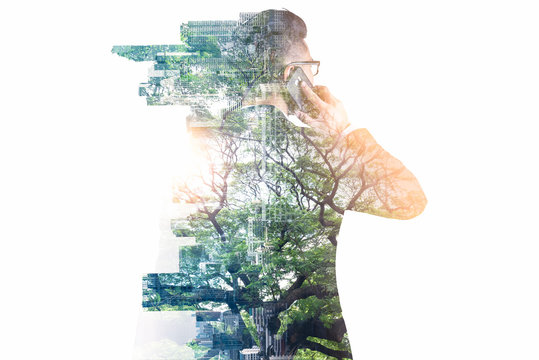 The double exposure image of the businessman using a smartphone during sunrise overlay with nature and cityscape image. The concept of telecommunication, technology, 5g and internet of things.