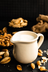 Homemade almond milk in jug. Almond milk and almonds