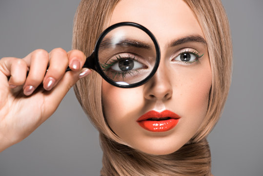 beautiful young woman holding magnifying glass and looking at camera isolated on grey