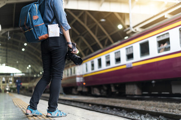 Back side of Young Asian traveling women holding camera and map traveling by train at Bangkok railway station, Thailand, traveler, tourist and photography concept