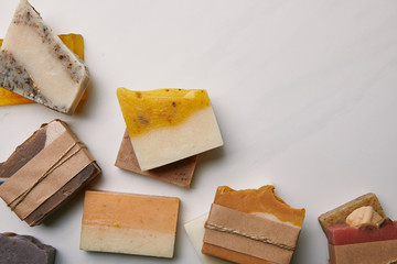 Obraz top view of various handmade soap pieces on white marble surface - fototapety do salonu