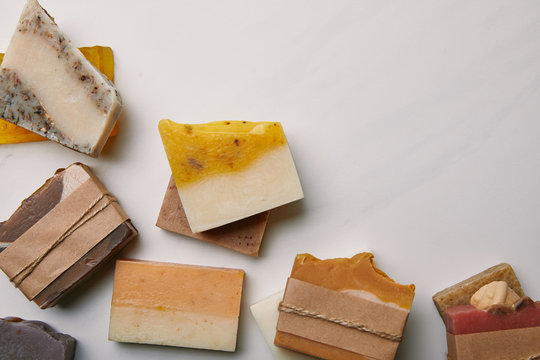 top view of various handmade soap pieces on white marble surface