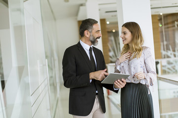 Young businesswoman and businessman look on digital tablet and discuss aout project