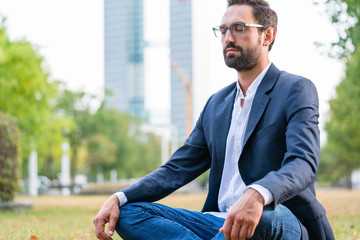 Close-up of calm businessman sitting in the park meditating