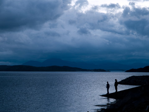 Fishing at dusk on Loch Alsh in the Western Highlands of Scotland with the Skye Bridge in the background