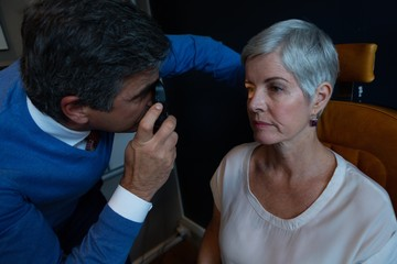 Optometrist examining patient eyes with ophthalmoscope