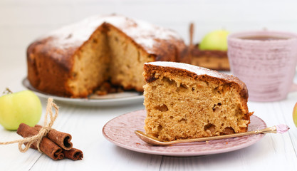Pie with apples, cinnamon and ginger on a white background. A piece of cake in the foreground. On the photo, apples, cinnamon sticks and a cup of coffee.