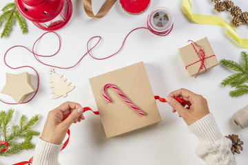 Christmas gift wrapping. Woman's hands packing Christmas present box on white table background